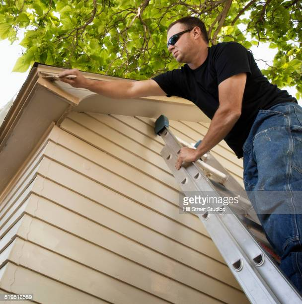 Man painting edge of roof