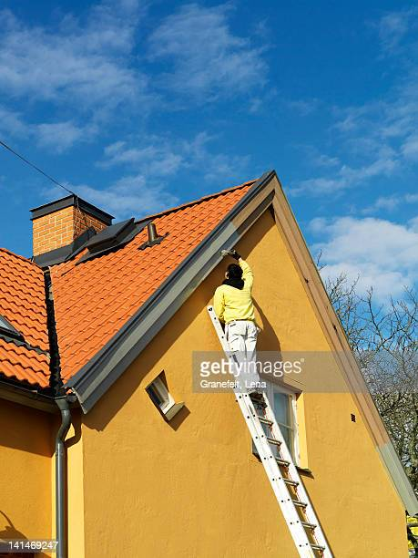 Man painting gable, low angle view