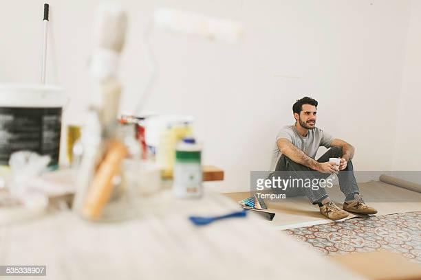 Homme peinture son pendant une pause tout en peinture de style appartement.