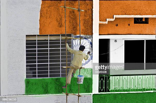 Man painting Indian flag on wall
