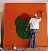 Man painting large canvas, rear view