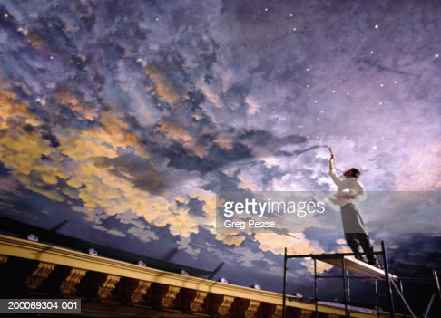 Man painting mural on ceiling low angle view stock photo for Constellation ceiling mural