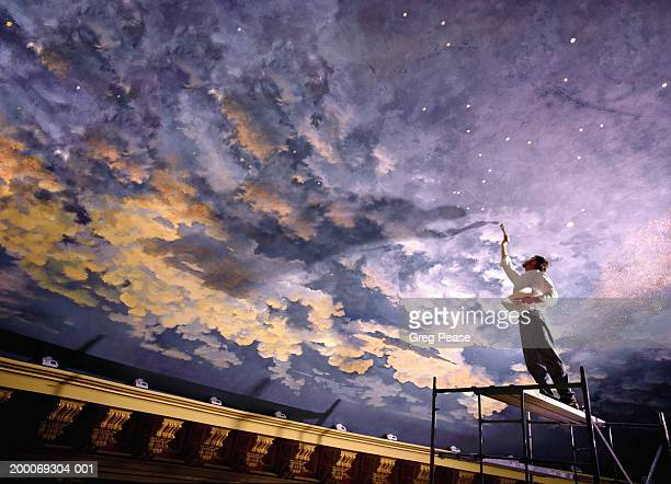 Man painting mural on ceiling, low angle view (digital composite)