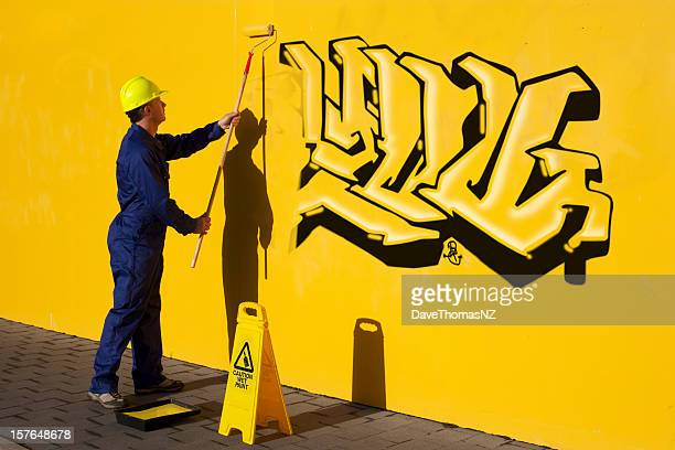 Man painting over graffiti on a  yellow wall.
