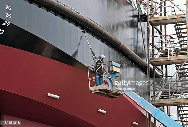 Homme peinture bateau au quai au sec