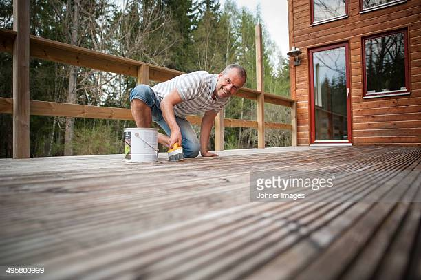 Man painting terrace dock, Ronneby, Blekinge, Sweden