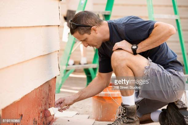 Man painting wall of house