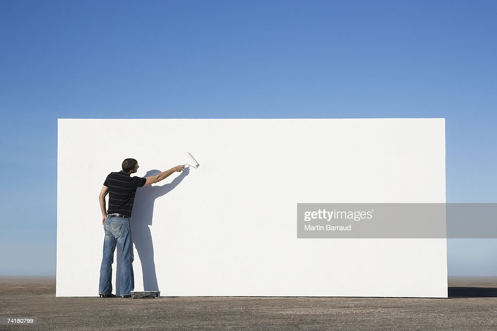 Man painting wall outdoors : Stock Photo
