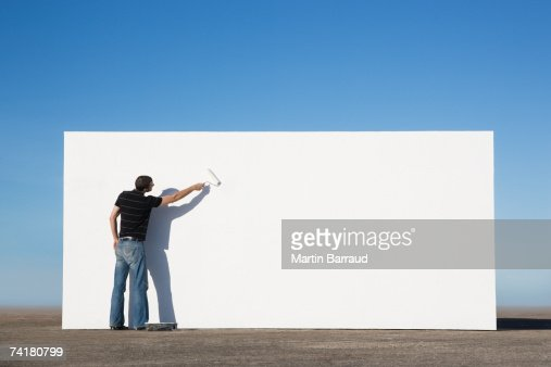 Man painting wall outdoors