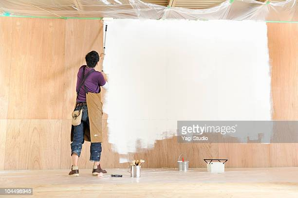 Man painting wall, rear view
