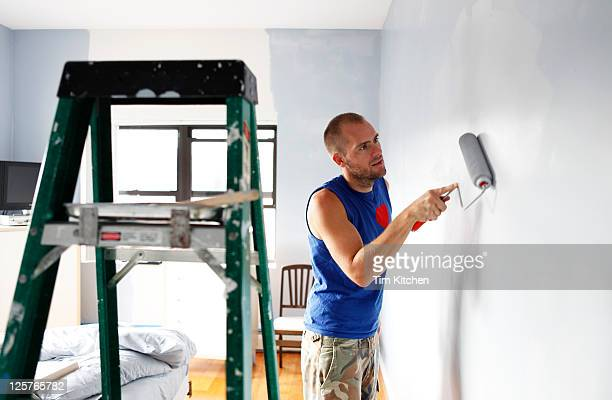 Man painting wall with roller