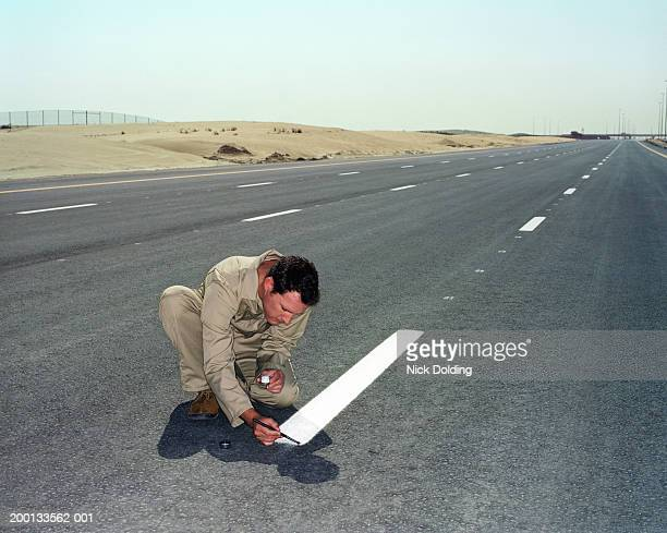 Man painting white line on road with small brush