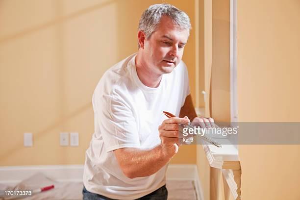 Man painting window sill