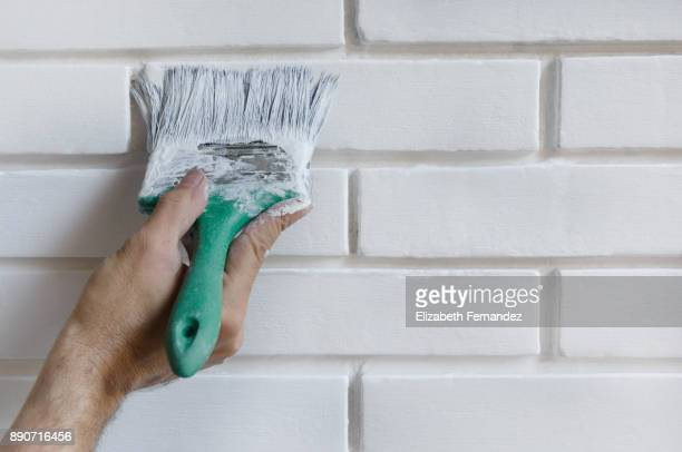 Man painting with brush brick wall on white color