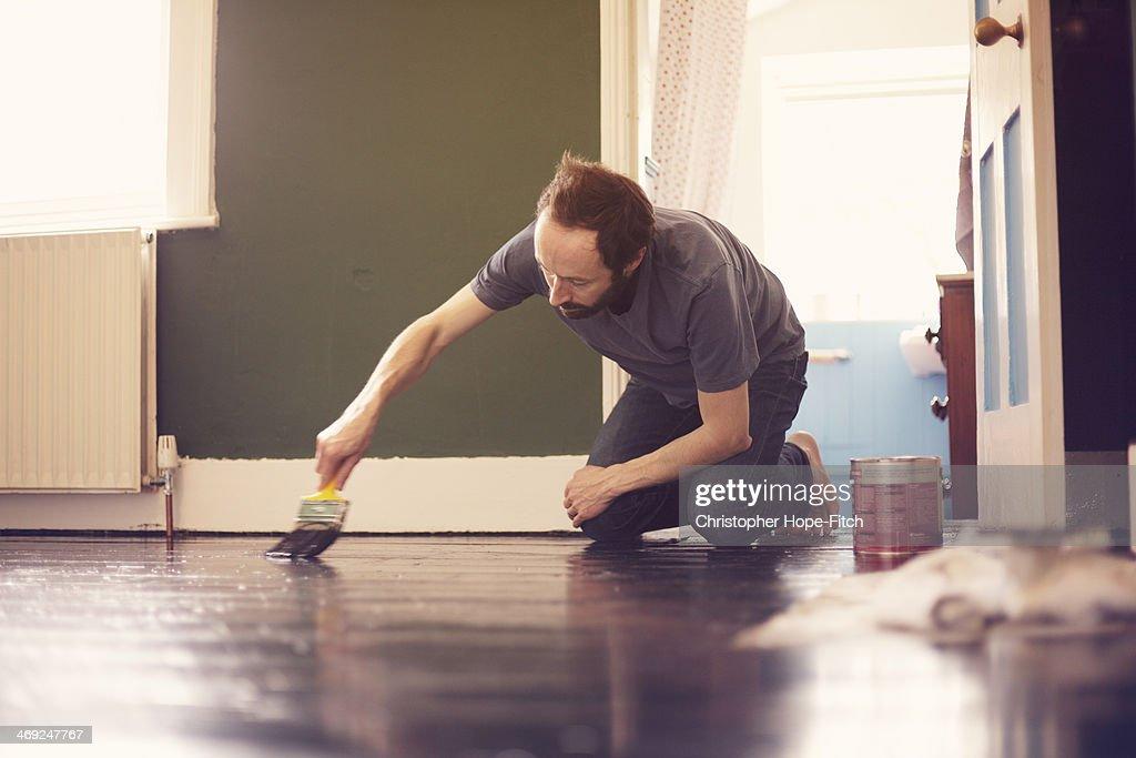 Man painting wooden floor : Stock Photo