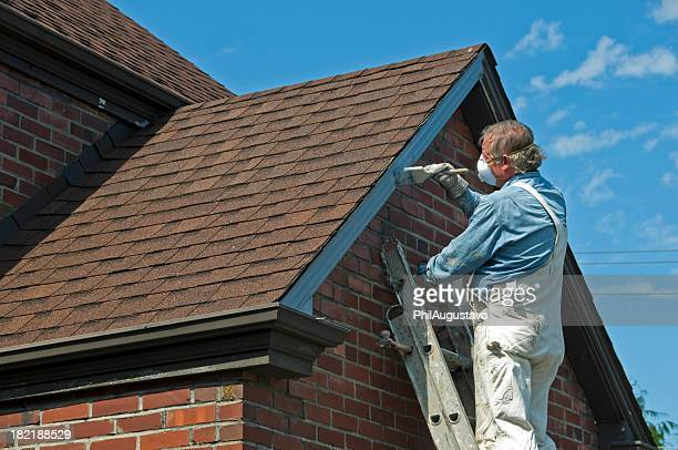 Man painting wooden trim of church