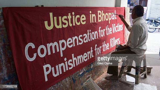 A man paints a banner for an upcoming march advocating social justice and reparations for the victims of the Bhopal gas leak November 30 2012 in...