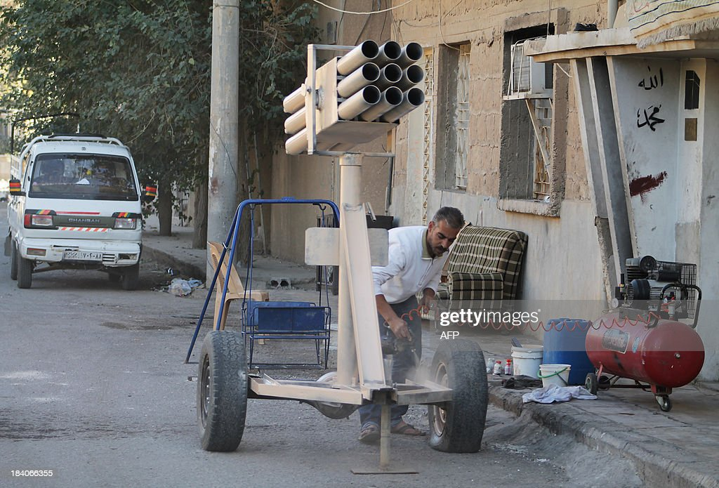 A man paints a homemade multi-rocket launcher in the Jubaila neighbourhood of Syria's northeastern city of Deir Ezzor on October 11, 2013. Jihadist fighters were accused of war crimes over the killing of 190 civilians from Syrian President Bashar al-Assad's Alawite minority as the Organisation for the Prohibition of Chemical Weapons (OPCW) tasked with eliminating the banned arms in Syria won this year's Nobel Peace Prize.
