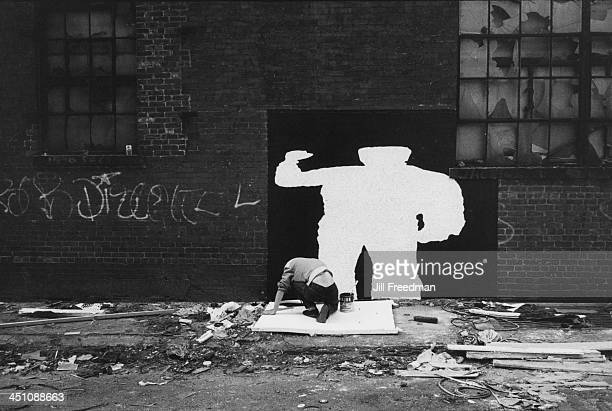 A man paints a silhouette of a man on a wall in New York City 1980