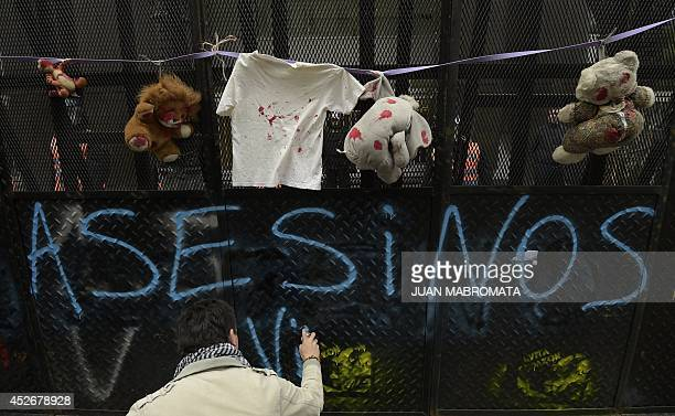 A man paints a slogan that partially reads 'Murderers' in support of Palestina on a fence with fake bloodstained toys hanging from it during a...