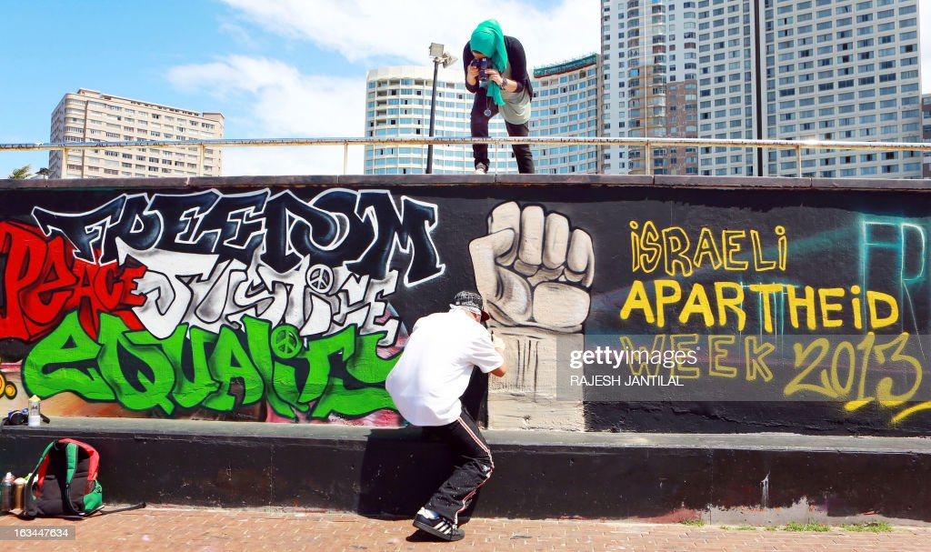 A man paints a wall at the north beach in Durban on March 10, 2013 ahead of the Israeli Apartheid Week (IAW) from March 11 to 17, 2013 in South Africa. The annual international series of events includes rallies, lectures, cultural performances, film screenings, multimedia displays and boycott of Israel actions held in cities and campuses across the globe.