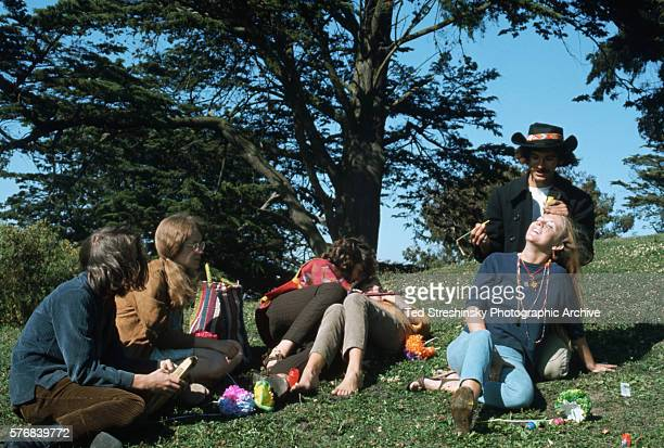 A man paints a woman's face during the Summer of Love in Haight Ashbury San Francisco California 1967