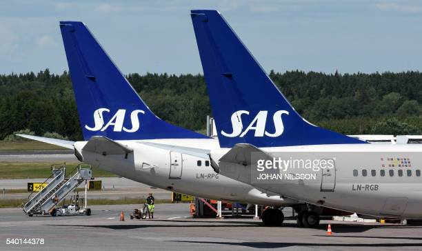 A man paints new lines behind the tails of two of Scandinavian airline Boeing 737 aircrafts parked at Terminal 4 during the SAS pilots strike at...