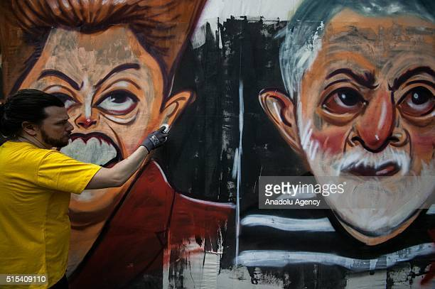 A man paints the portraits of the former president 'Lula' and Dilma Rousseff during a protest against President Dilma Rousseff government with the...
