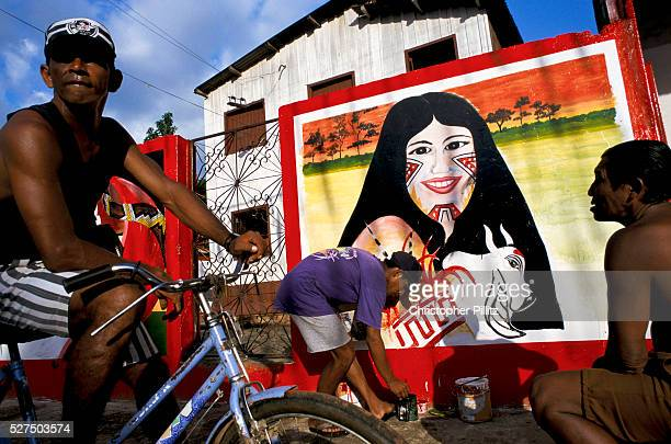 A man paits a wall mural of the 'Cunha Poranga' the queen of the 'Boi Bumba' Carnival Parintins Brazil The carnival serves to celebrate and reenact...