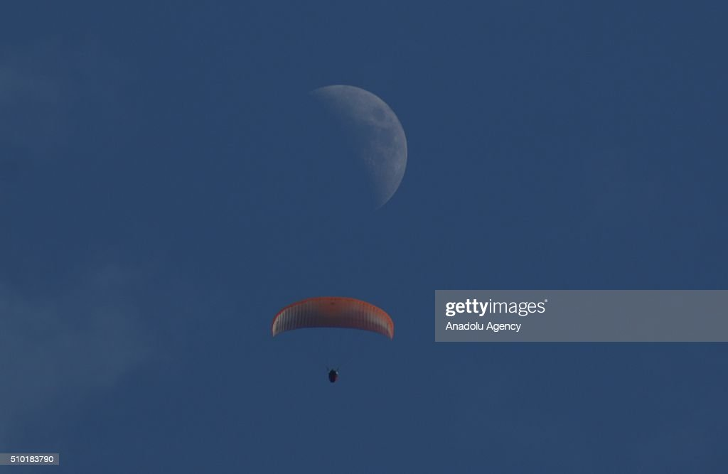 Man parachutes in the sky as moon is seen on the background in Iskenderun district of Hatay, Turkey on February 14, 2016.