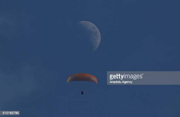 Man parachutes in the sky as moon is seen on the background in Iskenderun district of Hatay Turkey on February 14 2016