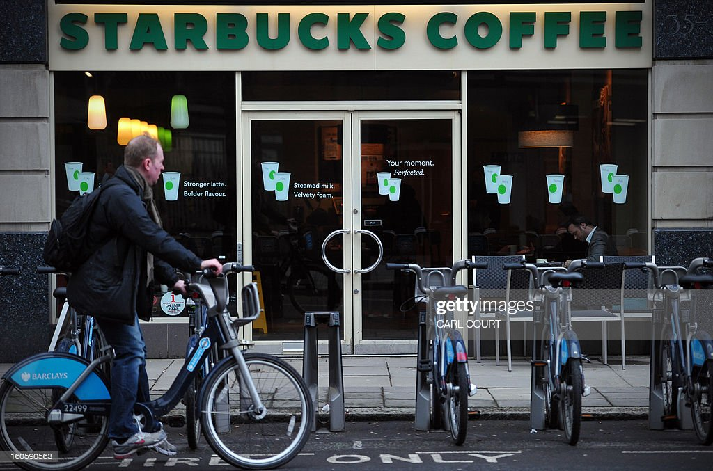 A man parks his hire bicycle outside a branch of Starbucks in central London on February 1, 2013. Despite pledging to pay millions of pounds in extra tax in Britain, Starbucks faces a battle to restore its reputation over its fiscal stance, with analysts saying the offer is 'too little too late'. AFP PHOTO / CARL COURT