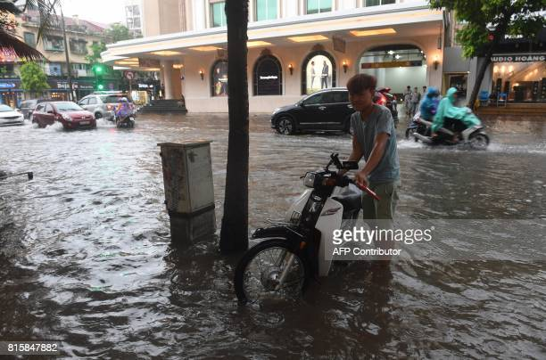 A man parks his motorcycle on a flooded street in Hanoi on July 17 after tropical storm Talas made landfall in northern Vietnam / AFP PHOTO / HOANG...