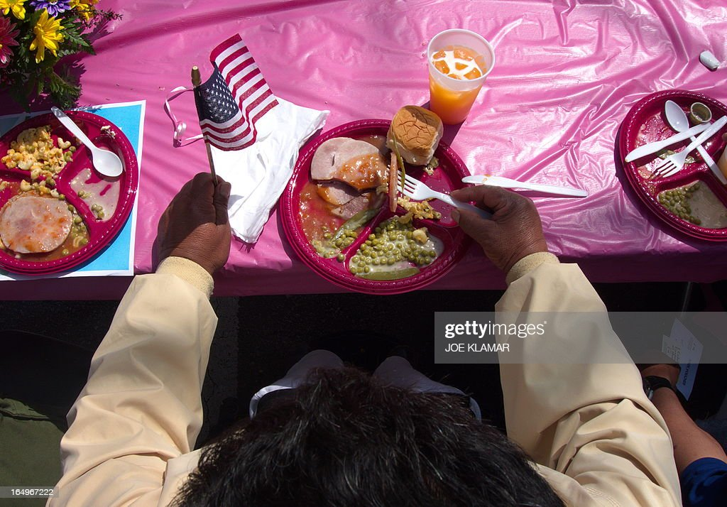 A man partakes of a free lunch during the Los Angeles Mission's Good Friday event on Skid Row on March 29, 2013 in Los Angeles, California. Celebrities and volunteers joined together in giving something back to this community of the homeless, among the largest in the US, who were fed a fully-prepared meal and had the opportunity to be given foot washing and hygiene kits. Foot washing, a symbolic ritual of humbleness and respect derived from Jesus Christ's washing of his disciples feet at the Last Supper, was offered by the Los Angeles Health Center and volunteers. AFP PHOTO/JOE KLAMAR