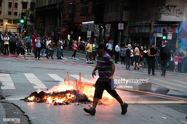 A man pass by a burning barricade after an eviction ended in violent clashes in downtown Sao Paulo The eviction occurred in a building that was...