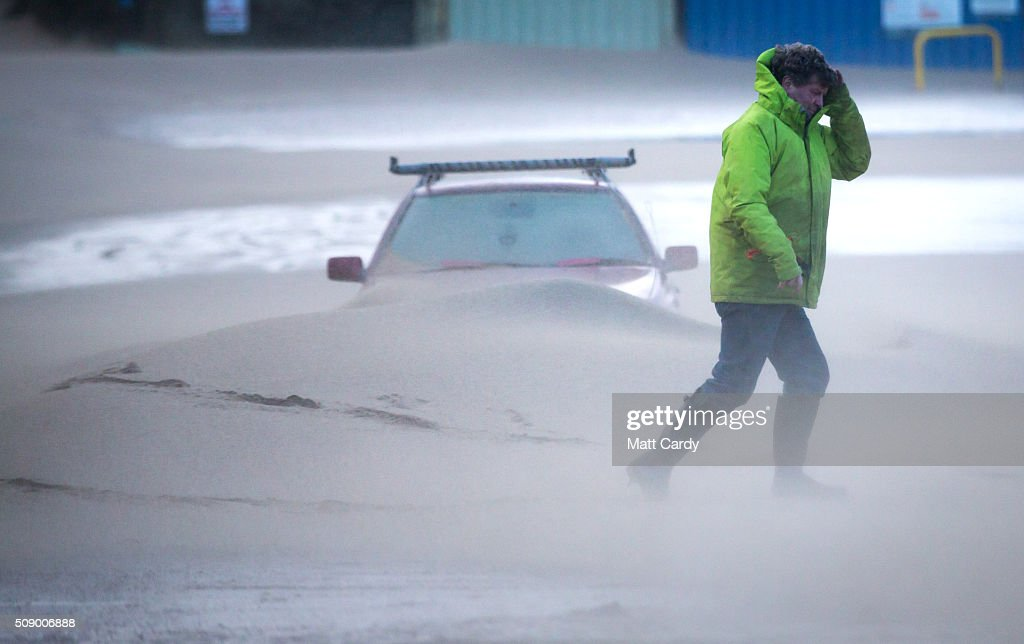 A man passes a car that has been partially covered in sand in Fistral Beach car park on February 8, 2016 in Newquay, England. Parts of the UK are currently being battered by Storm Imogen, the ninth named storm to hit the UK this season. Thousands of homes have been left without power and commuters hit by road and rail chaos as Storm Imogen batters the South with gale force winds and torrential rain.