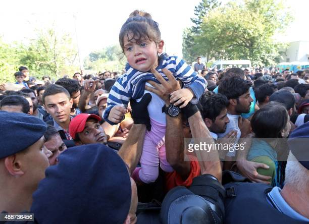 A man passes a child over to a police officer as they direct migrants and refugees onto buses at the train station in the city of Tovarnik close to...