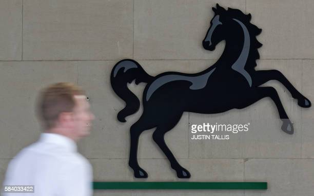 A man passes a Lloyds logo outside the entrance to an office of Lloyds Banking Group in the City of London on July 28 2016 British bank Lloyds will...