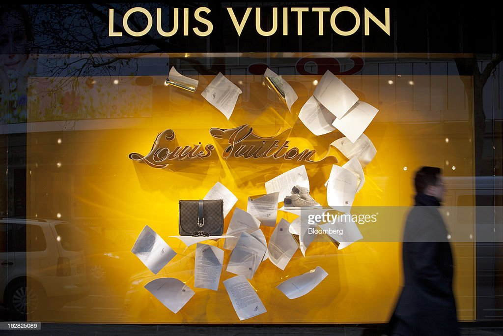 A man passes a Louis Vuitton store, operated by LVMH Moet Hennessy Louis Vuitton SA, in Berlin, Germany, on Wednesday, Feb. 27, 2013. German unemployment unexpectedly fell in February amid signs that Europe's biggest economy is returning to growth after a contraction at the end of last year. Photographer: Balint Porneczi/Bloomberg via Getty Images