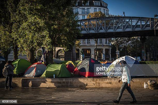 A man passes a migrant tent camp next to the Stalingrad metro station in Paris on November 3 one of several camps sprouting up around the French...