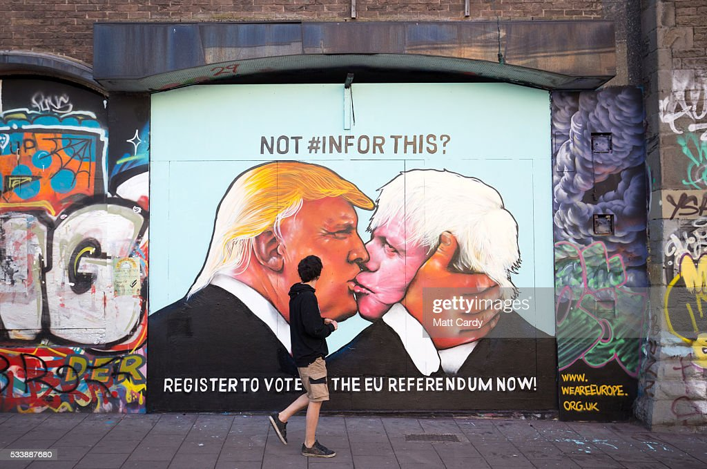 A man passes a mural that has been painted on a derelict building in Stokes Croft showing US presidential hopeful Donald Trump sharing a kiss with former London Mayor Boris Johnson on May 24, 2016 in Bristol, England. Boris Johnson is currently one of the biggest names leading the campaign for Britain to leave the European Union in the referendum which takes place on June 23 and Republican presidential hopeful Donald Trump has also backed a so-called Brexit.
