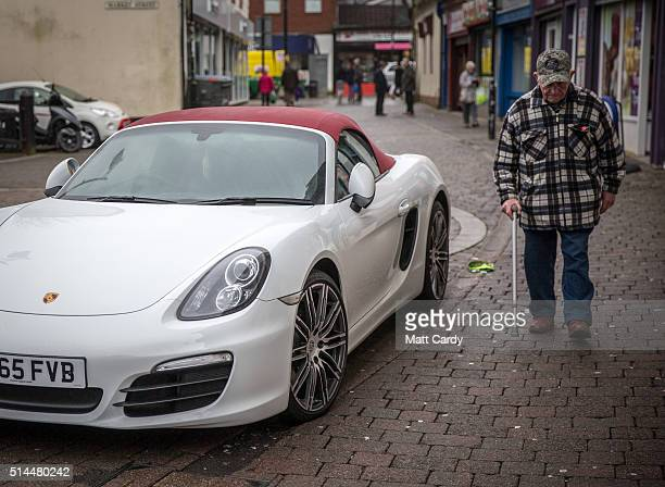 A man passes a Porshe sports car parked outside a licensed premises in Aberdare on March 8 2016 in Rhondda Cynon Taf Wales The West Wales and the...