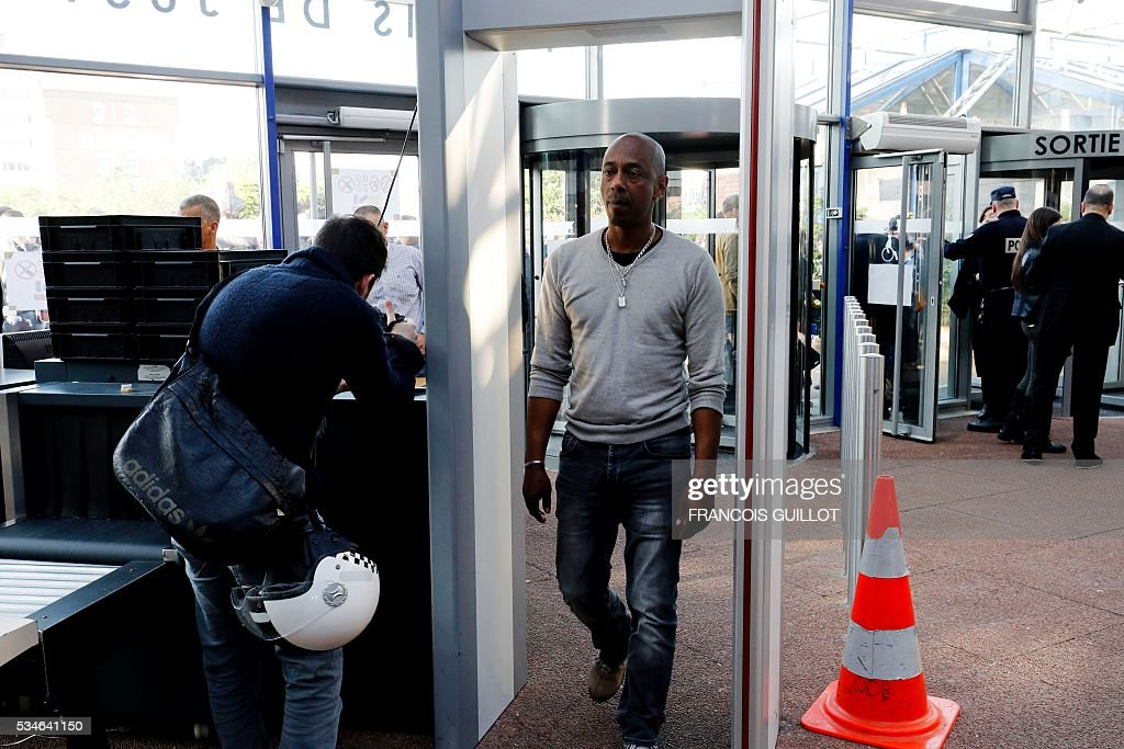 A man passes a security gate at the court of Bobigny, northern Paris on May 27, 2016 during the trial of 15 French CGT union's members judged for the episode of the torn shirt, in full showdown initiated by the union with the government on labor law. On October 5, 2015 under the cries of naked, naked and resignation , the Air France human resources director found himself shirtless, tattered shirt during a protest after the announcement of a restructuring of the airline threatening nearly 3,000 jobs.