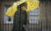 A man passes a window covered in rain drops on October 6 2014 in Bath England After one of the warmest and driest September months in recent years...