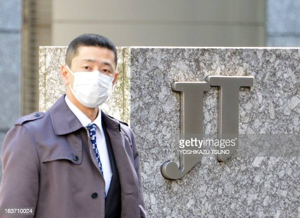 A man passes before a logo of Japanese cigarette maker Japan Tabacco at the company's headquarters in Tokyo on March 15 2013 Japan Tobacco said that...