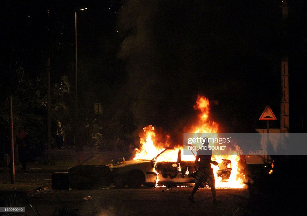 A man passes by a burning car as demonstrators face riot police in the city of Le port, west of the French island of La Reunion, on February 18, 2013, on the sideline of a demonstration to demand government-subsidized contracts. The demonstrators blocked in the morning the main road between the north and the south of the island but after one hour of riot later in the day, the traffic start again without any injuries.