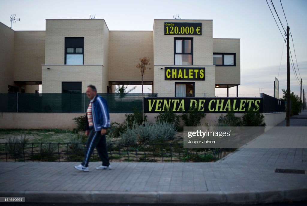 A man passes by a chalet for sale from 120.000 Euro's on October 22, 2012 in Sesena, Spain. With a housing backlog of more than 1.2 million unsold newly build homes, banks in Spain have recenlty started to sell their real estate assets with discounts, some upto 80 percent, slashing prices to a level not seen for over 20 years. With morgages of 100 percent, some experts worry that mistakes from the past are repeated again.