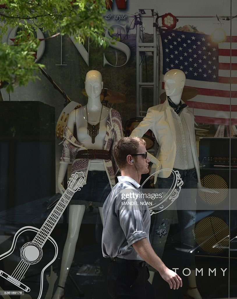A man passes by a department store on May 31, 2016 in Washington, DC. US consumer confidence fell for the second straight month in May amid apparent caution over the economic situation, the Conference Board said May 31, 2016. / AFP / MANDEL