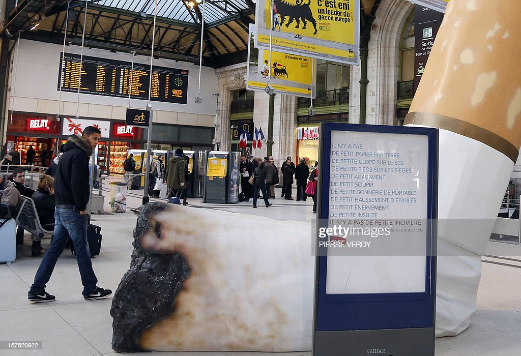 A man passes by a giant mock-up discarded cigarette displayed on the ground at the Gare de Lyon railway station in Paris, on December 4, 2012, as part of a public-awareness campaign launched by France's national rail company SNCF to shed light on commuters' disrespectful behaviour.