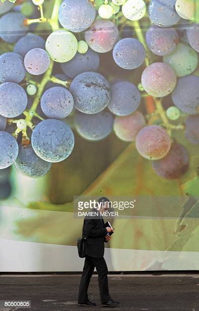 A man passes by a giant picture of grapefruit at the first day Vinitaly wine exhibition in Verona on April 3 2008 Vinitaly will welcome 4300...